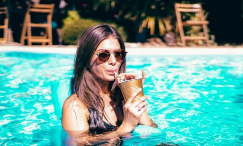 Woman in pool with a cool drink